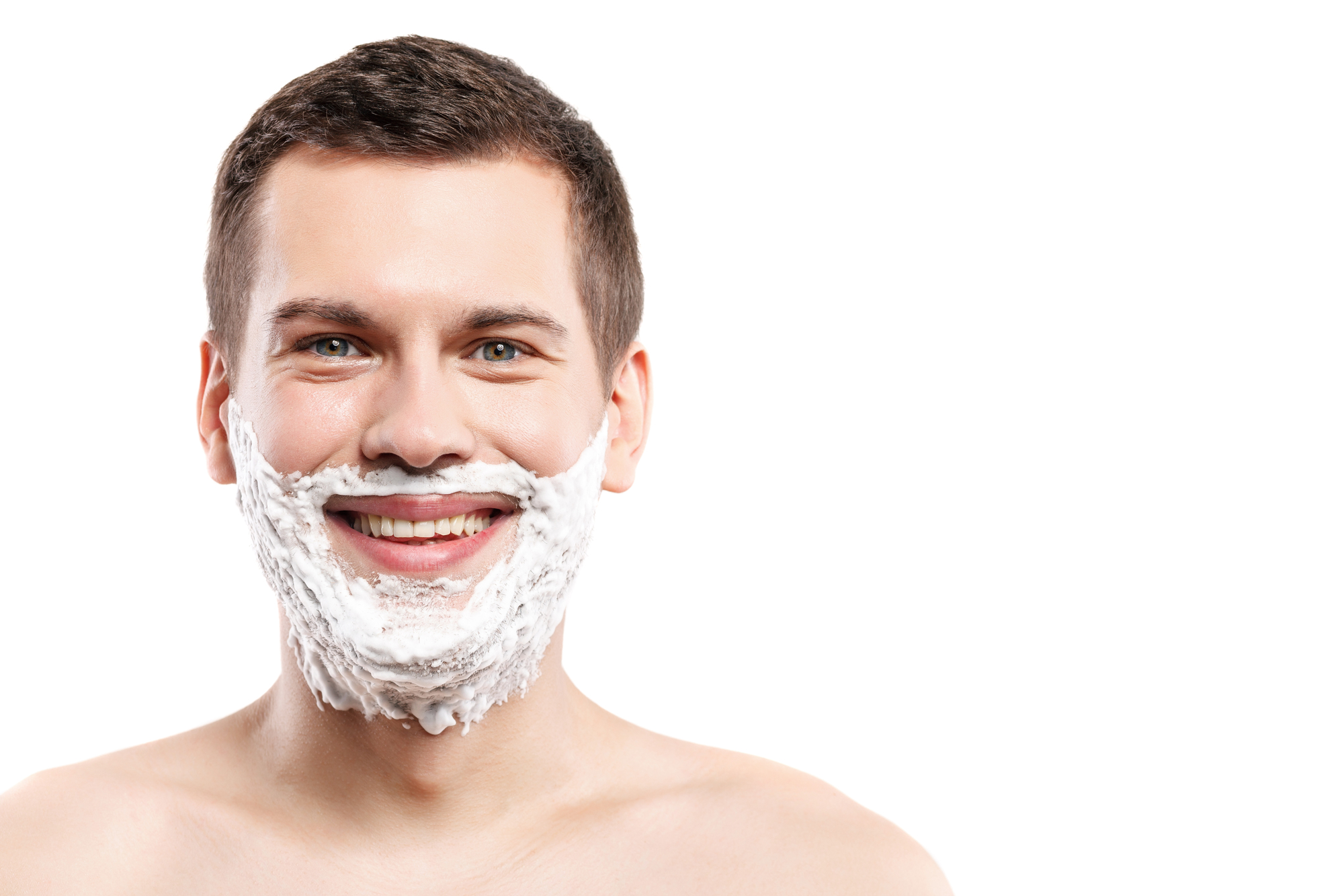 Portrait of happy young man with shaving cream on his chin. He is standing and smiling. Isolated and copy space in right side