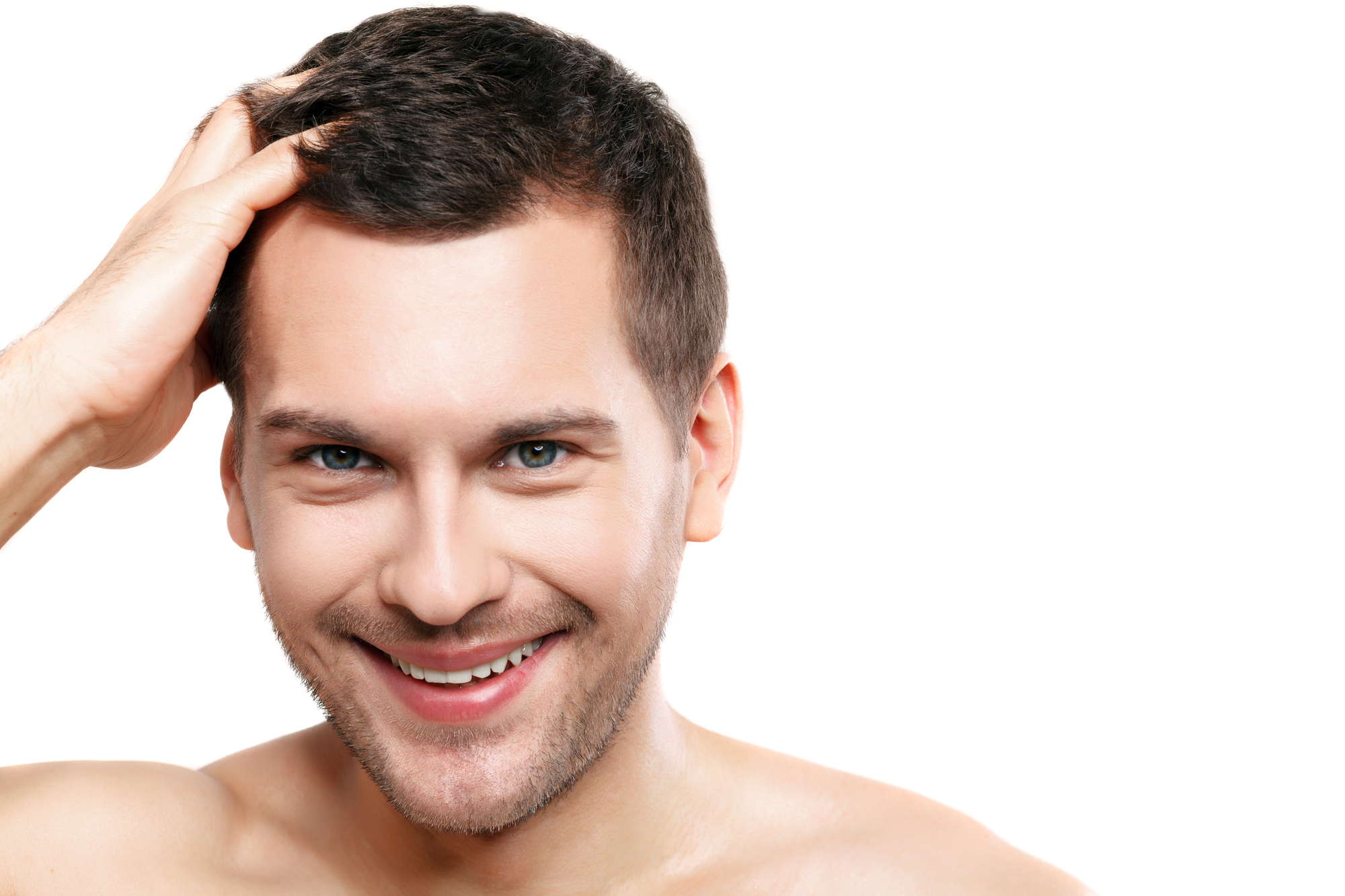Portrait of attractive young man touching his hair and smiling. He is standing and looking at camera happily. Isolated and copy space in right side