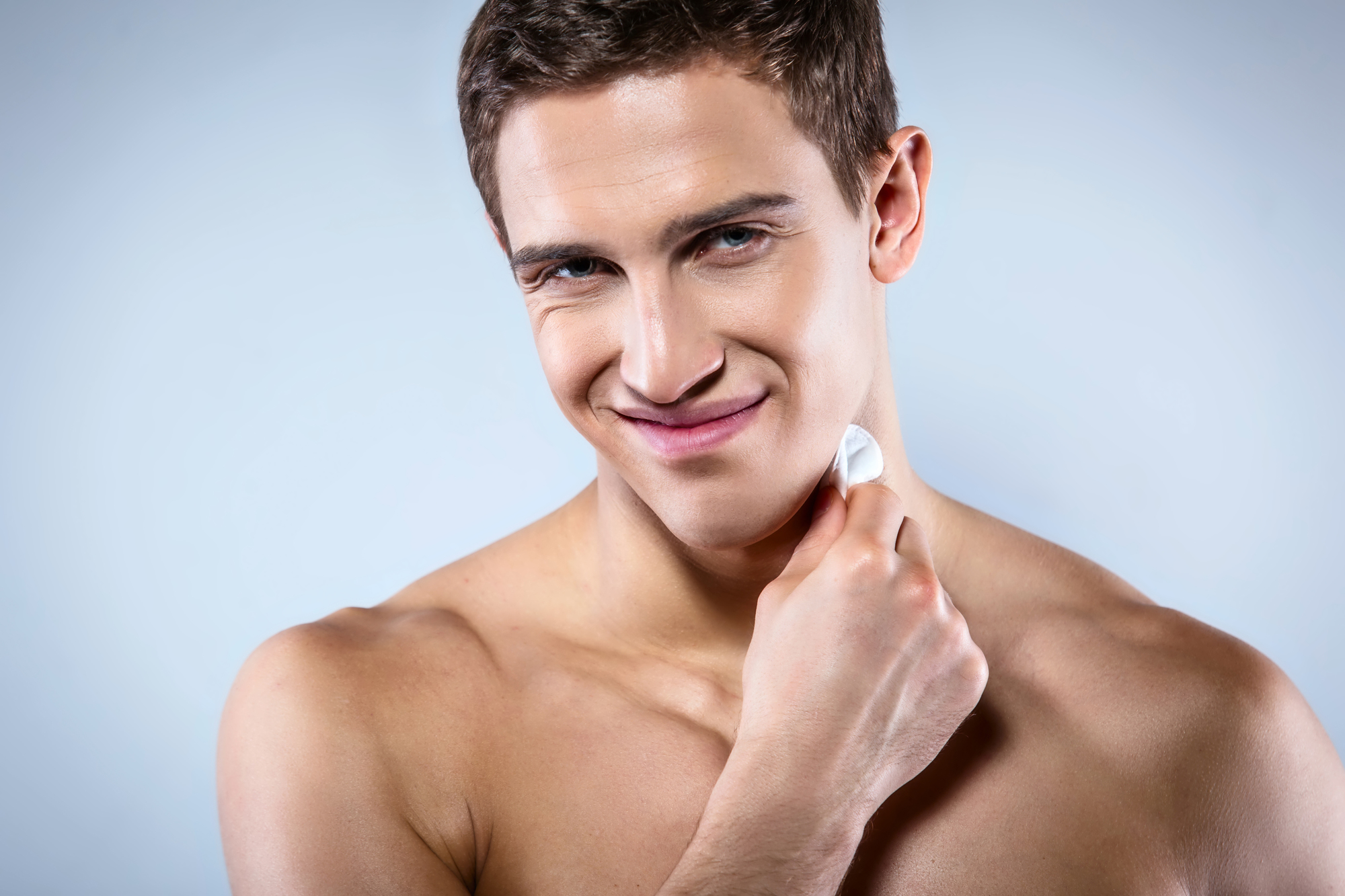 Studio shot of handsome young man with naked torso. Muscular man looking at camera and wiping face with lotion and cotton pad