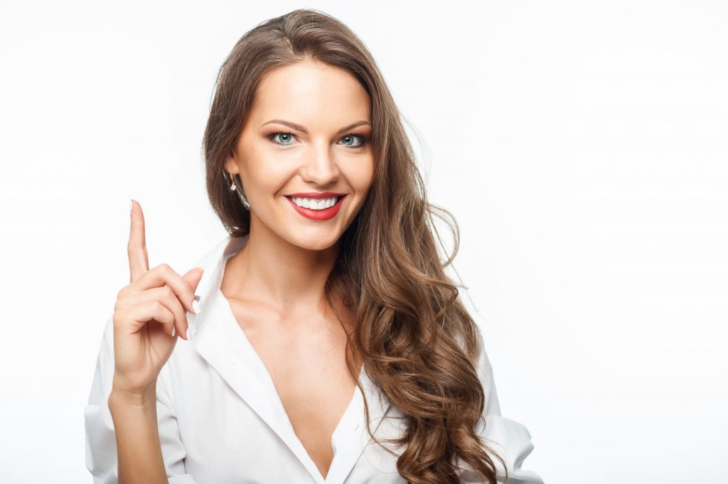 Cheerful girl is pointing her index finger up. She is smiling confidently. Isolated on background and copy space in right side