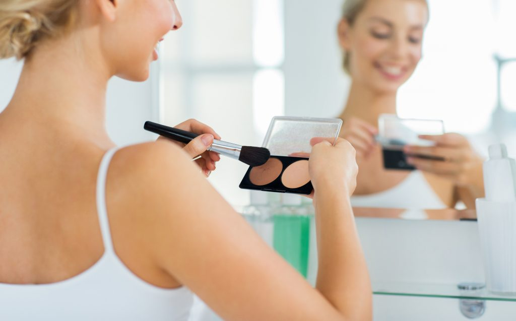 beauty, make up, cosmetics, morning and people concept - close up of happy young woman with makeup brush and contouring and highlighting palette looking to mirror at home bathroom