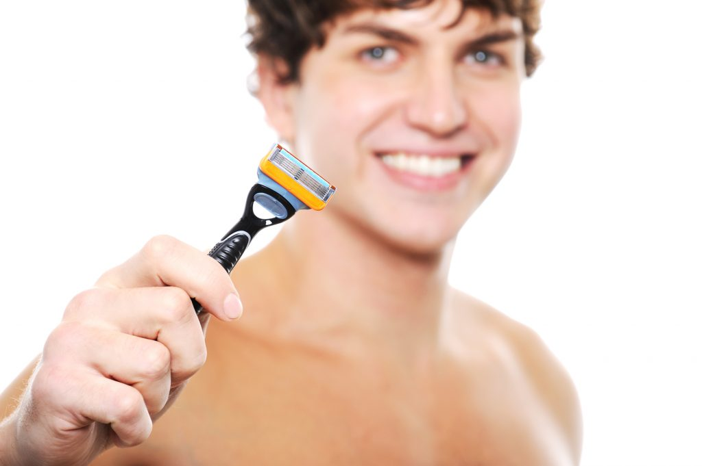 Happy laughing clean-shaven face of young man with razor in the hand  on foreground