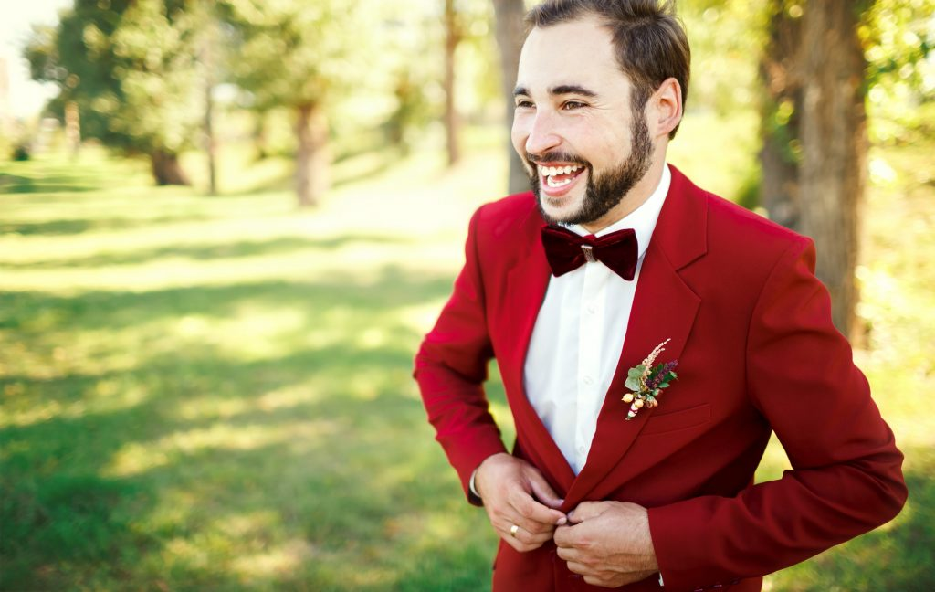 Stylish groom portrait in tuxedo suit marsala red, burgundy bow tie, a professional hairstyle, beard, mustache. Wedding preparations, groom getting ready. Copy space for text. Celebration.